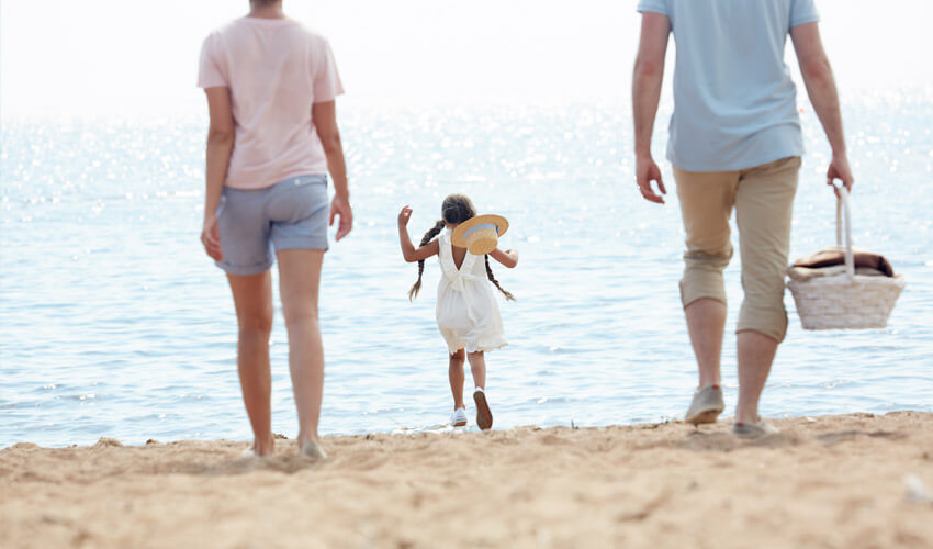 Familia paseando por la playa de Menorca